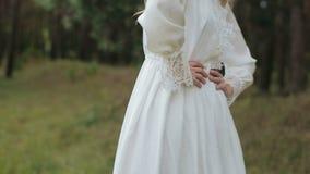 Mooi meisje in het witte kleding stellen aan de camera dichtbij groen bos stock footage