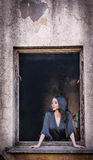 Mooi meisje in het zwarte stellen in een oud raamkozijn Aantrekkelijk lang haar donkerbruin dagdromen in het rotten de bouw stock foto