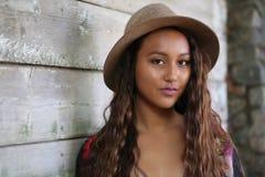 Mooi meisje in hoed door een houten muur royalty-vrije stock foto