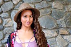 Mooi meisje in hoed door een rotsmuur stock fotografie