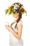 Mooi meisje in hoed van bloemen en kop thee Royalty-vrije Stock Foto's