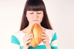 Mooi meisje holding en het bijten brood van brood Royalty-vrije Stock Afbeeldingen