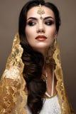 Mooi meisje in Indische stijl met een sjaal op haar hoofd Model met een creatieve en heldere make-up Stock Foto's