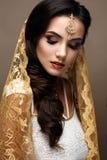 Mooi meisje in Indische stijl met een sjaal op haar hoofd Model met een creatieve en heldere make-up Stock Afbeeldingen