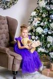 Mooi meisje 4 jaar oud in een blauwe kleding Baby in Kerstmisruimte met teddybear, grote klok, Kerstmisboom, bruine leunstoel, stock fotografie