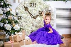 Mooi meisje 4 jaar oud in een blauwe kleding Baby in Kerstmisruimte met teddybear, grote klok, Kerstmisboom, bruine leunstoel, stock afbeeldingen