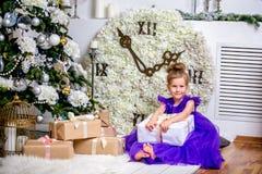 Mooi meisje 4 jaar oud in een blauwe kleding Baby in Kerstmisruimte met teddybear, grote klok, Kerstmisboom, bruine leunstoel, stock afbeelding