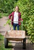 Mooi meisje in jeans en overhemd met kruiwagen bij rustieke geep Stock Foto