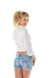 Mooi meisje in jeans korte en witte die blouse op wit wordt geïsoleerd Stock Foto's