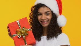 Mooi meisje in Kerstmanhoed tonen huidig aan camera, Kerstmisviering stock footage