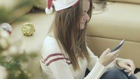 Mooi meisje in Kerstmis GLB die smartphone achter Kerstmisboom gebruiken stock footage