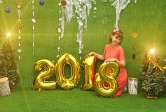 Mooi mooi meisje in kleding met aantallen van nieuw jaar 2018 en stock fotografie