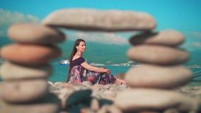 Mooi meisje in kledingszitting op het strand Beeld door een kader van kiezelstenen wordt genomen die Erachter is het overzees, be stock footage
