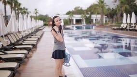 Mooi meisje in kleren en met een rugzak die dichtbij de pool lopen stock video