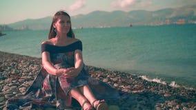 Mooi meisje in kleurrijke kledingszitting op het strand Achter het meisje is het overzees en de bergen stock footage