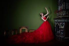 Mooi meisje in lange rode kleding en in koninklijke kroon Royalty-vrije Stock Foto's