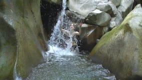 Mooi meisje in langzame motie die duidelijk water van bergmeer en blikken bespatten aan camera met kleine waterval in groen stock videobeelden