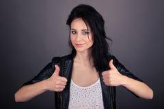Mooi meisje in leerjasje dat gebaren met haar handen toont royalty-vrije stock fotografie