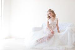 Mooi meisje in lingeriezitting op een wit laaghuwelijk Stock Fotografie