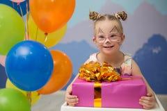Mooi meisje met benedensyndroom met een verjaardagsgeschenk stock foto's