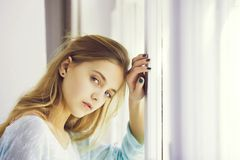 Mooi meisje met blauwe ogen die zich bij venster bevinden royalty-vrije stock foto