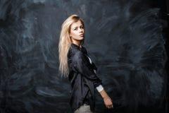 Mooi meisje met blondehaar in zwart modieus overhemd een varkenskot Royalty-vrije Stock Foto