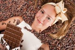 Mooi meisje met chocolade op cacaobonen Royalty-vrije Stock Afbeelding