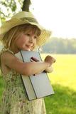 Mooi meisje met de Bijbel in aard stock fotografie