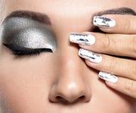 Mooi meisje met de zilveren make-up en de spijkers stock afbeelding