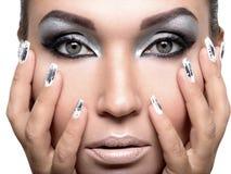 Mooi meisje met de zilveren make-up en de spijkers stock foto's