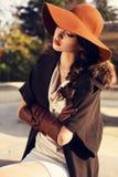 Mooi meisje met donker haar die elegante laag, hoed en handschoenen dragen royalty-vrije stock foto