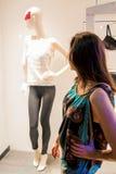 Mooi meisje met donker haar die zich voor een luxeopslag bevinden en een model bekijken Royalty-vrije Stock Afbeeldingen