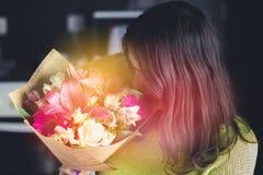 Mooi meisje met donker haar met een boeket van bloemen van een lelie, een gerbera, witte rozen en een alstroemeria op een donkere Royalty-vrije Stock Foto