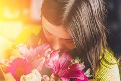 Mooi meisje met donker haar met een boeket van bloemen van een lelie, een gerbera, witte rozen en een alstroemeria op een donkere Royalty-vrije Stock Afbeelding