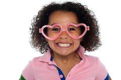 Mooi meisje met een brede grijns. Het dragen van grappig frame stock afbeelding