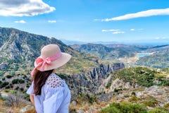 Mooi meisje met een brede hoed, die zich met haar terug op een achtergrond van groene bergen bevinden Royalty-vrije Stock Foto