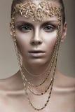 Mooi meisje met een bronshuid, een bleke make-up en ongebruikelijke toebehoren Het beeld van de kunstschoonheid Het Gezicht van d royalty-vrije stock foto