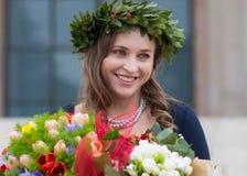 Mooi meisje met een diploma behaalde bloemen Stock Afbeeldingen