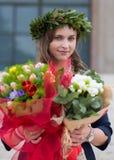 Mooi meisje met een diploma behaalde bloemen Stock Fotografie