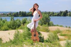 Mooi meisje met een gitaar in openlucht Stock Afbeelding