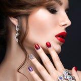 Mooi meisje met een heldere avondsamenstelling en een rode manicure met bergkristallen Spijkerontwerp Het Gezicht van de schoonhe Royalty-vrije Stock Foto