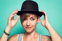 Mooi meisje met een hoed en een positieve houding stock fotografie