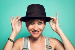 Mooi meisje met een hoed en een positieve houding stock afbeelding