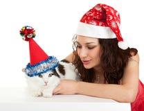 Mooi meisje met een kat in de kappen van het Nieuwjaar. Stock Afbeeldingen