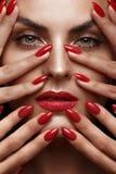 Mooi meisje met een klassieke samenstelling en rode spijkers Manicureontwerp Het Gezicht van de schoonheid royalty-vrije stock fotografie