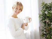 Mooi meisje met een kop in de ochtend Royalty-vrije Stock Foto's