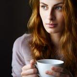 Mooi meisje met een kop in haar handen Stock Foto