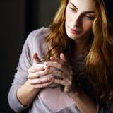 Mooi meisje met een kop in haar handen Stock Fotografie