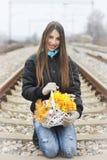 Mooi meisje met een mand bloemen het zitten Stock Fotografie