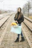 Mooi meisje met een mand van bloemen Stock Afbeelding